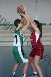 Foto de baloncesto que recoge a una niña que presiona el balón cuando el niño agota su bote en la defensa del hombre con balón