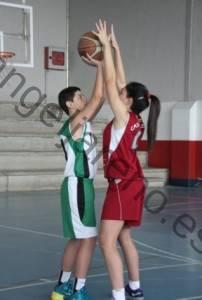 Foto de baloncesto que recoge a una niña pegada a un niño usando el cuerpo para poner presión sobre el balón en la defensa del hombre con balón