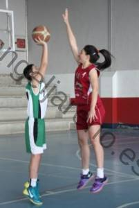 Foto de baloncesto que recoge a una niña saltando en vertical con la intención de presionar el tiro de un niño en la defensa del hombre con balón