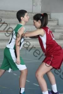 Foto de baloncesto que recoge a una niña bloqueando a un niño el rebote defensivo