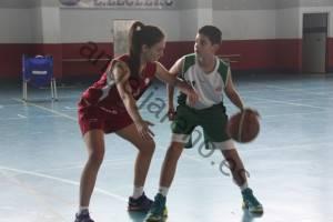 Foto de baloncesto de una niña defendiendo cerca a un niño que está botando un balón en la defensa del hombre con balón