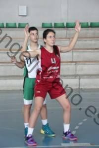 Foto de baloncesto que recoge el rebote defensivo con una niña dejando a su espalda a un niño