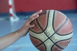 Foto de baloncesto que recoge una mano situada detrás del balón preparada para impulsarlo hacia adelante durante el bote