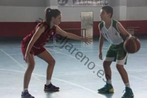 Foto de baloncesto que recoge a una niña defendiendo a un niño botando el balón a la distancia de un brazo en la defensa del hombre con balón