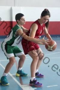 Foto de baloncesto de un niño defendiendo a una niña en el poste bajo en la defensa del hombre con balón