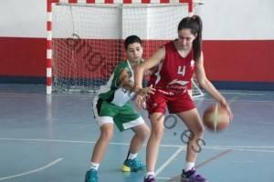 Foto de baloncesto de un niño defendiendo a una niña botando el balón en el poste bajo en la defensa del hombre con balón