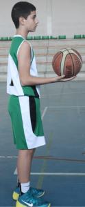 Foto de baloncesto de un niño de pie con un balón descansando en la palma de la mano, preparando el tiro