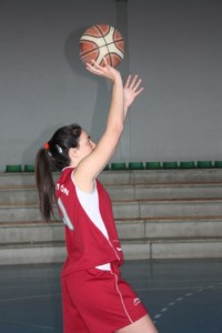 Foto de baloncesto de una niña en una entrada a canasta lanzando con una mano