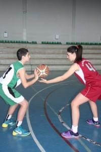 Foto de baloncesto de una niña defendiendo a un niño que todavía no ha botado el balón que es uno de los movimientos básicos