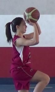 Foto de baloncesto de una niña en una entrada a canasta lanzando como un tiro, con dos manos