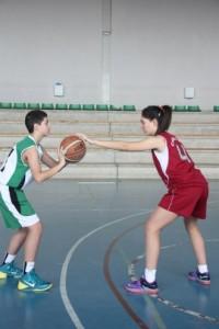 Foto de baloncesto que recoge a una niña defendiendo a un niño que todavía no ha botado que es uno de los movimientos básicos