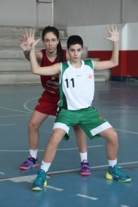 Fotografía de baloncesto que recoge los principios básicos ofensivos y a un niño en posición básica ofensiva de espaldas a la canasta dejando a su espalda a una niña que trata de defenderle