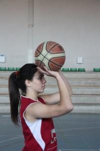 Foto de baloncesto de una niña con un balón preparada para hacer un tiro a canasta. mirando el aro