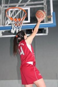 Foto de baloncesto de una niña realizando una entrada a canasta pasada con su mano interior