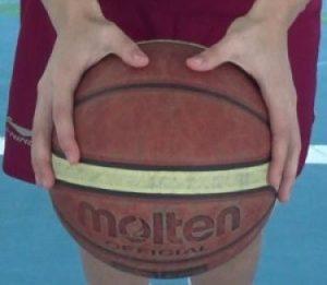 Foto de un balón de baloncesto cogido con las dos manos abiertas