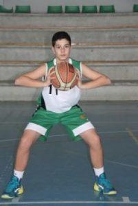 Foto de baloncesto de un niño agarrando el balón con las dos manos, pegado al pecho, justo debajo de la barbilla que es uno de los movimientos básicos