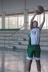 Foto de baloncesto de un niño cogiendo un balón de baloncesto en el aire con las dos manos que es uno de los movimientos básicos