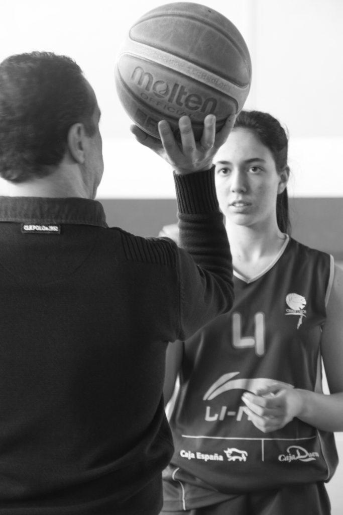 Foto de baloncesto que recoge a un entrenador y a una niña siguiendo un método para enseñar el tiro